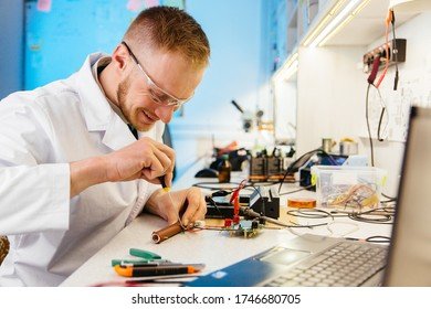 Happy, smiling man, technician, laboratory worker, testing and metering electronic cirquit board. Laptop in foreground.