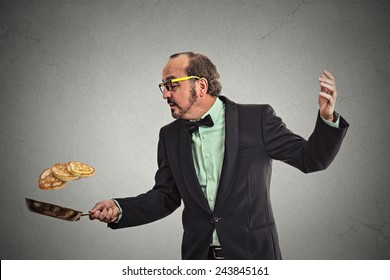 Happy smiling man tossing pancakes on frying pan isolated on grey wall background. Positive face expression emotion, Kitchen fun concept
