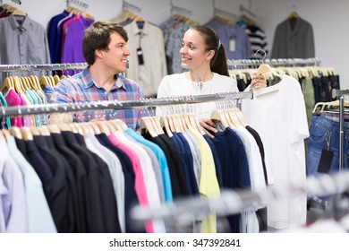 Happy smiling man and woman choosing clothing at the store