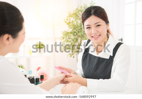 happy smiling manicurist makes the procedure for the care of nails by using polisher file. real salon spa background. beauty and fashion concept.