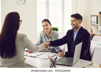 Happy smiling married couple making a handshake with a lawyer, realtor or financial advisor. Man and a woman consult an insurance broker or a bank employee in the office. Concept of respect and trust.
