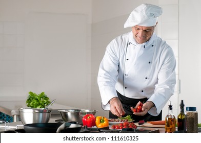 Happy smiling mature chef preparing a meal with various vegetables