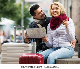 Happy smiling mature couple with suitcases and camera checking direction with map