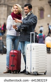 Happy smiling mature couple with suitcases, camera and map outdoors