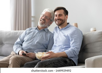 Happy smiling mature father wearing glasses and son watching tv show or movie together, eating popcorn snack, using remote controller, sitting on couch at home, two generations of men having fun
