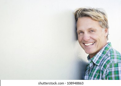 happy smiling mature man in forties leaning against a white wall.