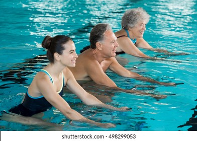 Happy smiling mature man and old woman cycling on a water bike in swimming pool. Happy and healthy senior people doing aqua aerobics on exercise bikes in a swimming pool. Fitness class training.