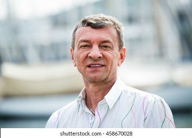 Happy smiling mature man outdoors at sunny spring day