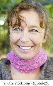 happy smiling mature woman with brown hair and green eyes wearing a pink scarf.