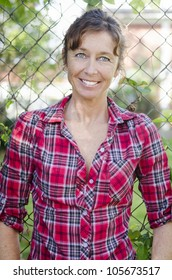 happy smiling mature woman in her forties wearing a red checked shirt.