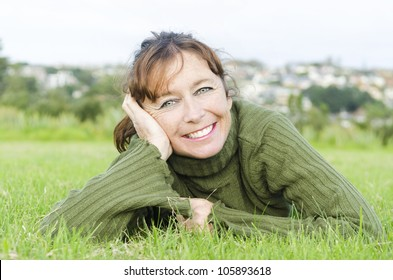 happy smiling mature woman laying on grass wearing a green sweater.