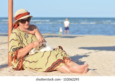 Happy smiling mature woman sitting & having fun outdoors on beach and knitting