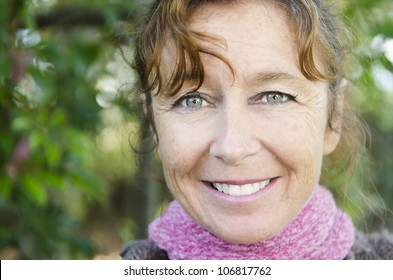happy smiling mature woman wearing a pink scarf