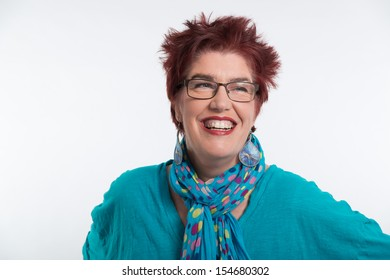 Happy smiling middle aged woman with red short hair and glasses. Wearing blue shirt. Studio portrait.