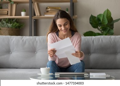 Happy smiling millennial girl holding paper document, received good news letter, university admission notification, last banking debt payment, high paid job offer, sitting on comfortable sofa at home.