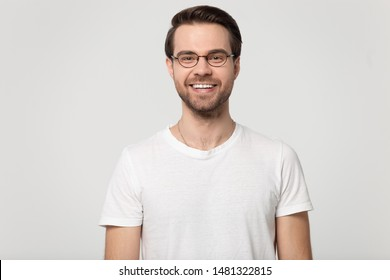 Happy smiling millennial guy wearing glasses head shot studio portrait, isolated on grey white background. Millennial satisfied handsome customer or employee posing for photo, looking at camera.