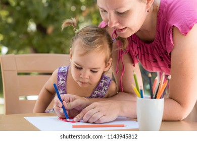 Happy Smiling Mother And Child Daughter Having Fun and Drawing Pictures Outdoors in Garden in Summer Season