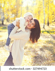 Happy smiling mother and child playing having fun in sunny autumn day