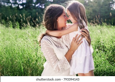 Happy smiling mother and daughter in white dresses hug each other. Happy family outdoors. Parenthood. Care. Happy Mother's Day. Hug day.
