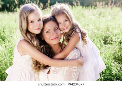 Happy smiling mother and daughters in white dresses outdoor. Daughters hug mother. Happy family outdoors. Mother's Day. Hug Day.