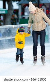 happy smiling mother and her cute cheerful son ice skating together at winter