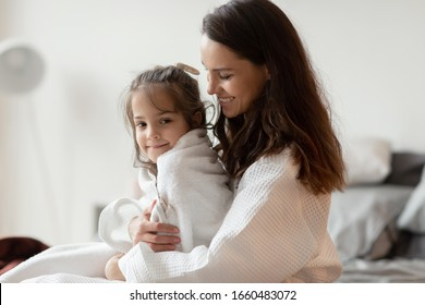Happy smiling mother holding loving daughter on knee. Young woman and child after shower rest in bedroom. Kid in towel and mom in bathrobe. Bedtime preparation. Parenting and children caress