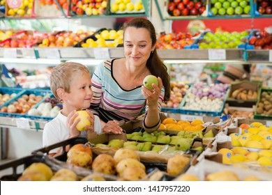 Happy smiling mother with little boy buying pears and apples at store