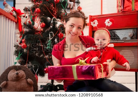 Happy smiling mother with little cute baby in red clothes in Christmas time  with gifts and 6fe271305