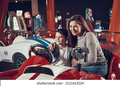 Happy smiling mother and son sitting on toy car. Spending holiday together with family. Entertainment center, mall, amusement park. Family rest, leisure concept.