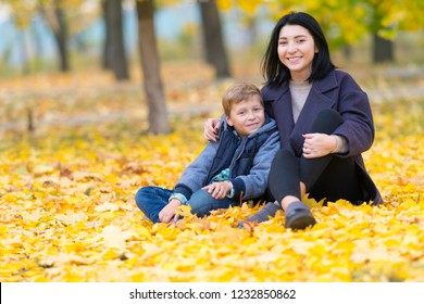 A happy, smiling mother and son sitting amongst yellow fall leaves in the park.