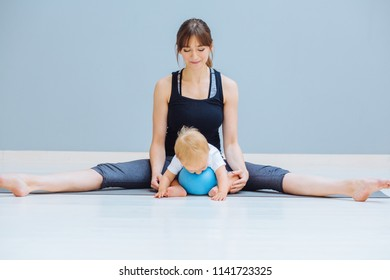 Happy smiling mother stretching legs. Mom training together with sweet positive emtions toddler blond baby boy at home over gray wall background. Fitness, maternity and healthy lifestyle concept.