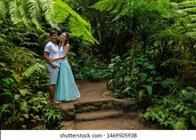 Happy smiling multiethnic couple hugging on walking trail in tropical forest. Young mixed race couple on honeymoon in Asia. Romantic relationship. Love story. Jungle rainforest. Ubud, Bali, Indonesia