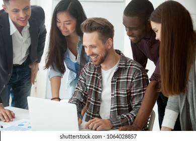 Happy smiling multi-ethnic creative millennial team excited by online result or growth, good news, business success looking at laptop laughing together got crowdfunding investment on startup project