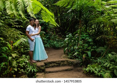 Happy smiling multiracial couple hugging on walking trail in tropical forest. Young mixed race couple on honeymoon in Asia. Romantic relationship. Love story. Jungle rainforest. Ubud, Bali, Indonesia