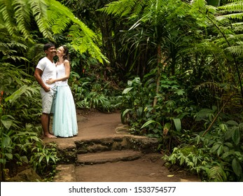 Happy smiling multiracial couple hugging and kissing on walking trail in tropical forest. Young mixed race couple on vacation in Asia. Romantic relationship. Love story. Jungle rainforest. Ubud, Bali