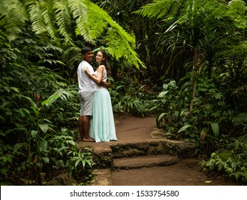 Happy smiling multiracial couple hugging on walking trail in tropical forest. Young mixed race couple on vacation in Asia. Romantic relationship. Love story. Jungle rainforest. Ubud, Bali, Indonesia