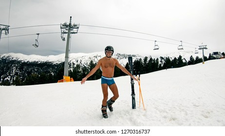 Happy smiling naked gay posing outdoors on ski slope during winter holiday