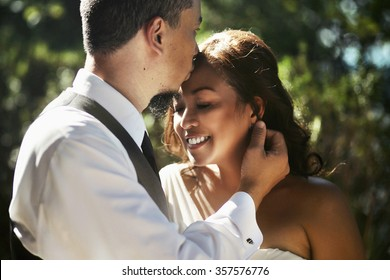Happy smiling newlyweds walking outdoors, kissing and embracing on their wedding day