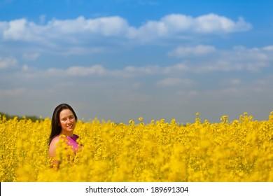 happy, smiling nice girl in rapeseed field