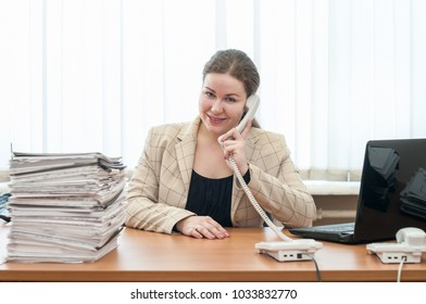 Happy smiling office assistant sitting at desk and calling by telephone