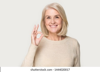 Happy smiling old lady showing ok sign headshot at studio. Elderly woman giving good advice, offer, help portrait isolated on grey background. Customer and client, sale, discount, business concept