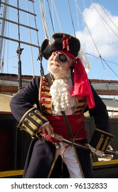 Happy smiling old pirate in colorful traditional costume stands on board ship and draws his sword. Schooner rigging and blue sky in background, vertical layout.