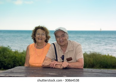 Happy smiling older couple outdoor by a lake