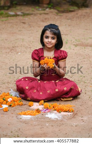 19e361418e509 Happy smiling playful young Indian / South Indian girl wearing traditional  dress holding flowers both hands