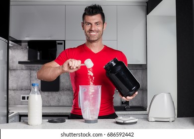 Happy smiling positive handsome sport looking man bodybuilder in red t-shirt with big black sports nutrition bank in the hand makes healthy protein milk cocktail in white hightech style kitchen