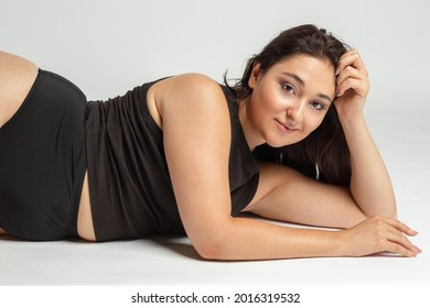 Happy smiling positive plus size woman. Face close up. Pretty caucasian female model dreaming at studio. Concept of beauty, body, skin care, healthy lifestyle, human emotions, wellbeing , spa.