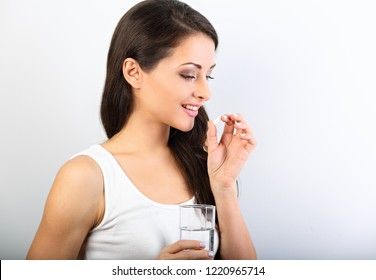 Happy smiling positive woman eating the pill and holding the glass of water in the hand on white background. Closeup profile view portrait.