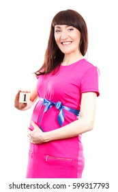 Happy smiling pregnant woman in pink dress with blue ribbon showing number of first month of pregnancy, concept of extending family and expecting for newborn