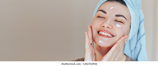 Happy smiling pretty beautiful woman girl with towel on head smiling touch healthy clean soft hydrated skin care after applying cream on young face natural beauty. without make up long banner