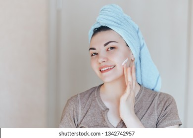 Happy smiling pretty beautiful woman girl with towel on head smiling touch healthy clean soft hydrated skin care after applying cream on young face natural beauty treatment. without make up